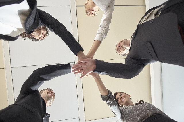 チームビルディングによって得られる効果 | メンバー同士で手を重ね合わせている画像